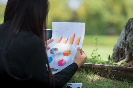 Asian entrepreneur business woman reading business graph analyze chart using laptop on green garden at home. Freelance working home office social distance new normal lifestyle in open cafe green park