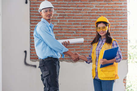 Civil Construction engineer teams shaking hands together wear work helmets worker on construction site. Foreman industry project working engineer teamwork. Two asian engineer team shake hands together
