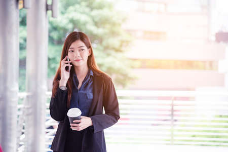 Business woman using smartphone shopping online, call, texting message internet technology lifestyle. Asian woman using cellphone walking on city street. Smart phone smart confident woman modern city