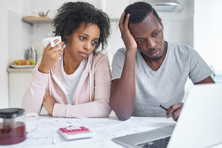 Young african american family, sitting at kitchen table. feeling unhappy because financial problem and economic crisis, trying to solve troubles, reviewing their finances using online bank application