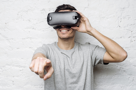 smile close up: Young handsome caucasian man wearing 3d glasses, pointing his fingers as if interacting with something. Smiling attractive man using VR headset, experiencing virtual reality while playing video game