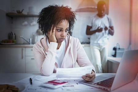 African female sitting at kitchen table, looking at her laptop, using online banking app to pay her debts, holding papers. Her husband standing with smartphone on backgrond. Financial problems concept