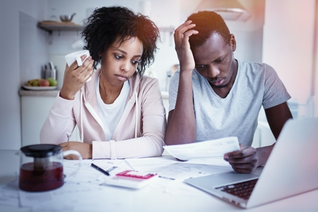 Stressed african american couple reviewing their finances sitting at kitchen table: wife and husband making calculations with papers and laptop. People and finances concept. Family budget and debts Archivio Fotografico