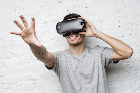 smile close up: Close up portrait of excited man experiencing virtual reality, using VR headset and touching air with his tattooed hand. Yound caucasian male smiling and gesturing as if interacting with something