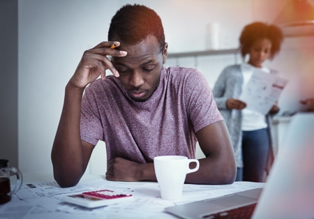 Unhappy african american family financial stress: black man sitting at kitchen, reading notification informing that bank denied to prolong loan term, his wife standing with bills in background