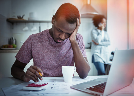 Sad african american man sitting with laptop at kitchen table, looking at bills, counting expenses, planning how to pay rent, stressed wife calling to bank at background. Household budget concept