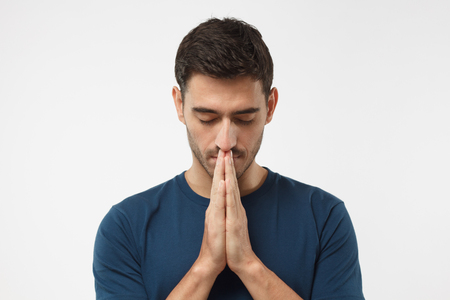 Closeup of young man isolated on gray background looking stressed, putting hands together as if he is praying with closed eyes to overcome depression and find solution to problem