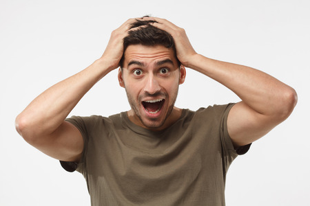 Headshot of handsome surprised manlooking at the camera, astonished with big sale prices, holding hands on head, standing against grey background. Human face expression concept 版權商用圖片