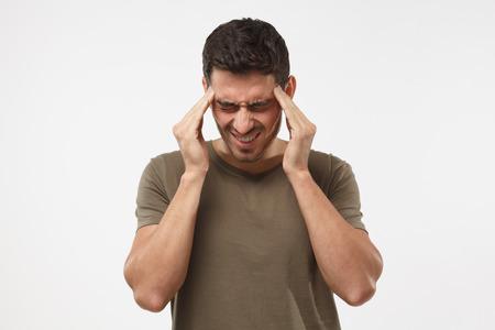 重度の頭痛に苦しむ灰色の背景に隔離された若者の肖像画は、寺院に指を押し付け、無力な顔の表情で痛みを和らげるために目を閉じる