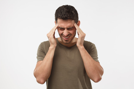 Retrato do homem novo isolado no fundo cinzento que sofre da dor de cabeça severa, pressionando os dedos aos templos, fechando os olhos a fim aliviar a dor com expressão impotente da cara