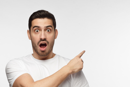 Horizontal photo of young Caucasian man pictured isolated on gray background dressed in white T-shirt looking at camera with mouth and eyes open with surprise, pointing right, copyspace for advert Banque d'images - 108682366