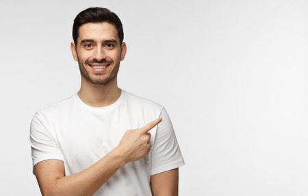 Attractive young man in white t-shirt pointing right with his finger isolated on gray background Stock fotó