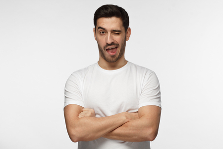 Studio shot of good looking man isolated on grey background looking enterprising and enthusiastic, winking friendly as if inviting to adventure or recommending good benefit