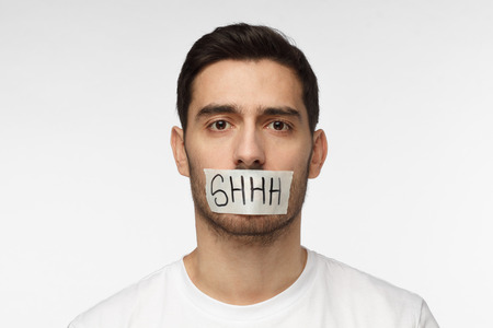 Close up shot of young man with taped mouth with shhh text on it