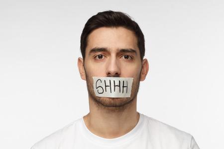 Immagine ravvicinata di giovane uomo con la bocca con nastro adesivo con testo shhh su di esso