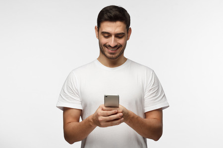 Horizontal photo of young good-looking European man pictured isolated on grey background dressed in casual blank T-shirt holding smartphone with bond hands and smiling positively while looking at it