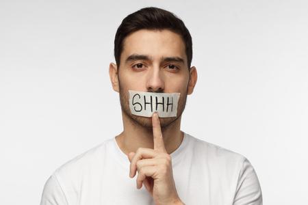 Immagine ravvicinata di giovane uomo con shhh gesto e bocca con nastro adesivo, chiedendo silenzio o di essere tranquillo, isolato su sfondo grigio