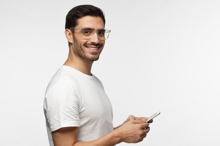 Side portrait of young handsome European Caucasian man isolated on gray background with transparent safety glasses on, holding tablet computer in hands with open positive smile, ready to help