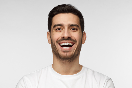 Close up horizontal shot of handsome unshaven young man in white tshirt laughing out loud, smiling broadly