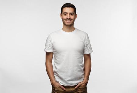 Joven europeo de pie con las manos en los bolsillos, vestido con camiseta blanca en blanco con espacio para copiar su logotipo o texto, aislado sobre fondo gris