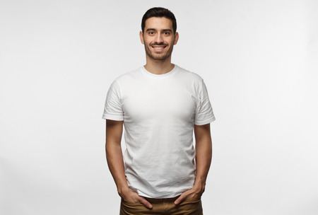 Young european man standing with hands in pockets, wearing blank white tshirt with copy space for your logo or text, isolated on grey background