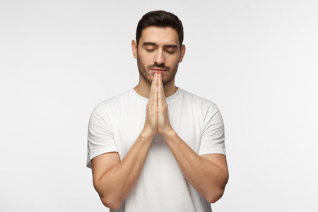 Closeup picture of handsome European man isolated on grey background in white casual T-shirt standing with closed eyes and hands pressed together as if meditating or praying, looking peaceful Foto de archivo