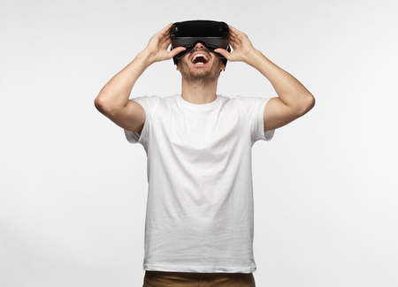 Horizontal half-length portrait of young European man pictured isolated on gray background wearing white T-shirt and virtual reality headset having lifted head up, laughing happily and having fun