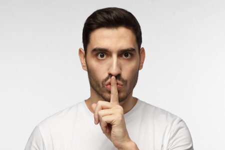 Horizontal photo of handsome European man isolated on gray background dressed in white casual T-shirt pressing finger to lips as if asking to keep silence, not willing anyone to know secret 版權商用圖片