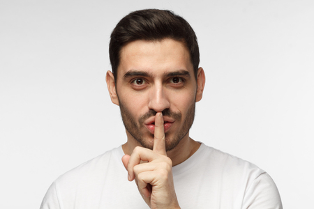 Close up shot of handsome tricky man with shh gesture, asking for silence or to be quiet, isolated on gray background Foto de archivo
