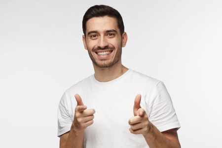 Closeup portrait of young happy European Caucasian man isolated on gray background smiling while looking at camera pointing to viewer with fingers of both hands as if approving and feeling pleased