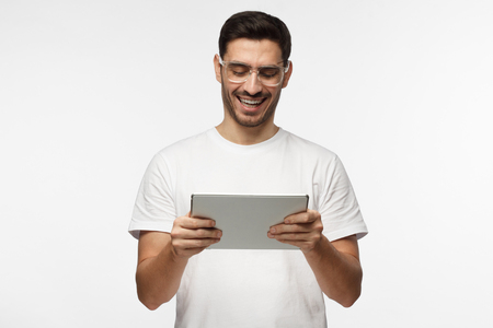 Closeup picture of good-looking European man pictured isolated on grey background looking through trendy transparent glasses at screen of tablet computer he is holding in hands in front of him