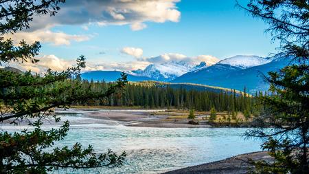 Daybreak over the Athabasca River near the town of Jasper in Jasper National Park in the Canadian Rocky Mountains under a beautiful partly cloudy sky Stock Photo