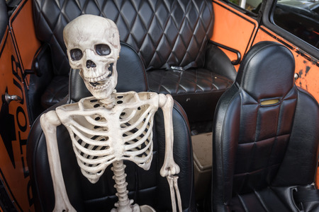 Laughing skeleton in the passenger seat of a car, ready for a ride on the Day of the Dead or Dia de los Muertos