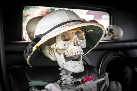 dia de los muertos: Laughing skeleton in the passenger seat of a car, ready for a ride on the Day of the Dead or Dia de los Muertos