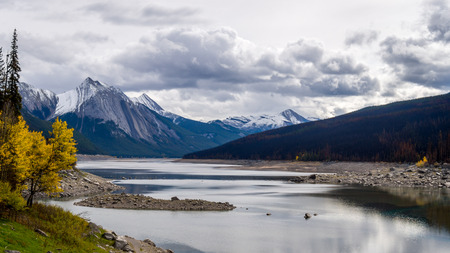 Medicine Lake in Jasper National Park. The lake drains underground into the Maligne River every fall and refills again in spring from fresh melting snow. Results of 2015 Forest Fire visible Stock Photo