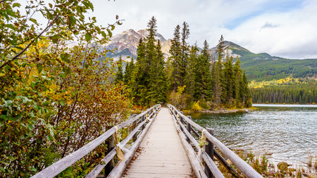 foot bridge: Foot Bridge in Pyramid Lake to Pyramid Island with Pyramid Mountain in the background in Jasper National Park in Canada