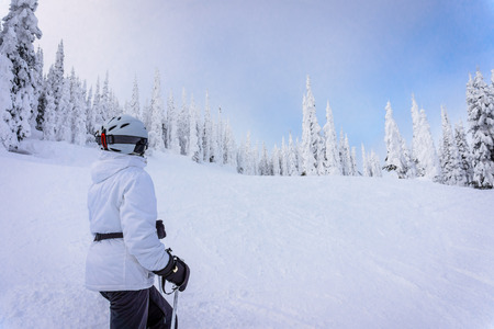 Skier enjoying the view of snow covered trees in the high alpine of the Shuswap Highlands in central British Columbia