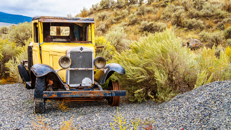 oldie: Abandoned and damaged vintage Yellow Car in a Field in the semi desert area of central British Columbia