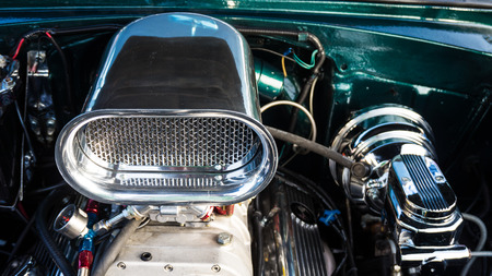 intake: Close up of an air intake on an engine of a vintage car on display at a car show