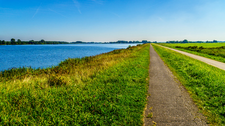 straight path: Straight Bike Path over the Dike along the Veluwemeer near the town of Nijkerk in the Netherlands