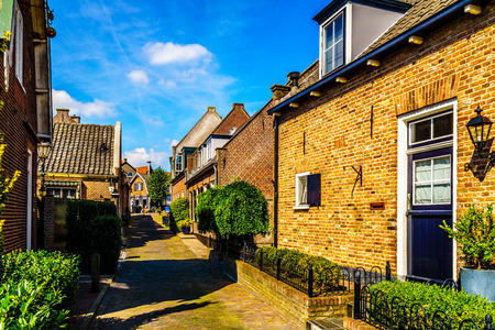 neighbourly: Quiet street in the historic Dutch Fishing Village of Bunschoten-Spakenburg with Renovated Row Houses on a Sunny Summer day