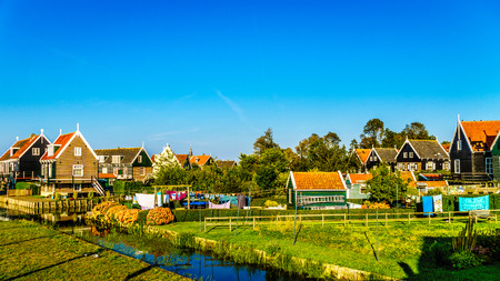 renovated: Traditional houses with green boarded wall and red tile roof in the small historic fishing village of Marken in the Netherlands Stock Photo