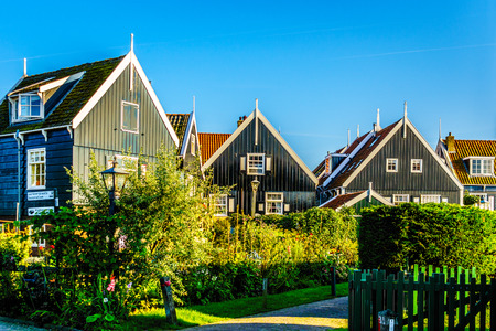 Traditional houses with green boarded wall and red tile roof in the small historic fishing village of Marken in the Netherlands Stock Photo