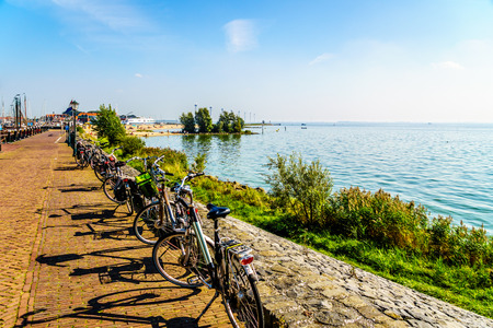 water mill: Typical Dutch Bikes parked at the promenade along the inland sea named IJselmeer seen from the historic fishing village of Urk in the Netherlands