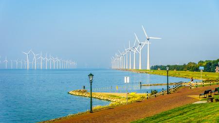 Windmolenpark in de binnenzee genoemd IJselmeer gezien vanuit het historische vissersdorpje Urk in Nederland Stockfoto - 73760188