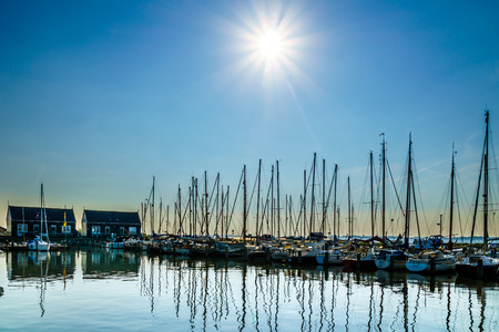 Sunset over the moored sail boats in the harbor of the historic small fishing village of Marken in the Netherlands