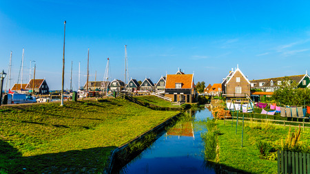 View of the harbor area with the traditional red roof houses surrounding it in the small historic fishing village of Marken in the Netherlands