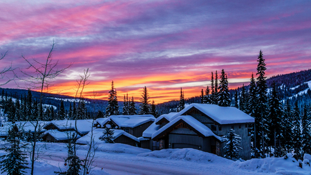 Sunrise and a glowing red sky over the snow covered houses of the alpine village of Sun Peaks in the Shuswap Highlands of central British Columbia, Canada