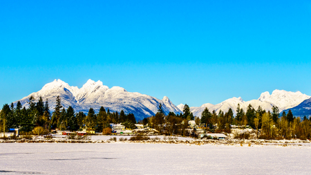 covered fields: The snow covered peaks of the Golden Ears mountain and Mount Robie Reid behind the town of Fort Langley in the Fraser Valley of British Columbia, Canada on a cold winter day and snow covered fields