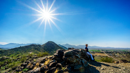 sates: Senior woman enjoying the view from the top of the National Trail as the Sun is casting its sun rays on the mountains of South Mountain Park in Maricopa County near the city of Phoenix, Arizona, USA